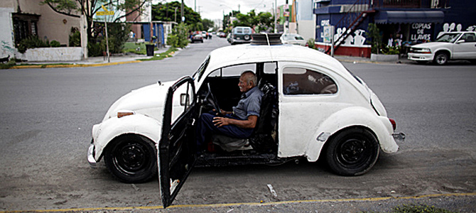 Oscar Almaguer sits in his VW Beetle 1967 in Apodaca